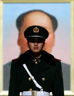 policeman in front of a picture of Mao...